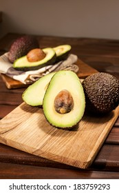 Many ripe halved avocados on wooden cutting board. Still-life.