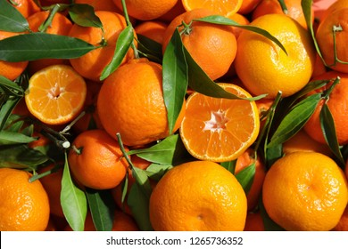 Many ripe tangerines with leaves as background, top view
