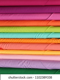 Many rolls of colorful cotton material cloth on the shop's wholesale store specializing in colorful fabrics