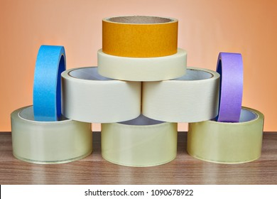 Many rolls of scotch packing tape, and masking tape is stacked in form of pyramid, on orange background.