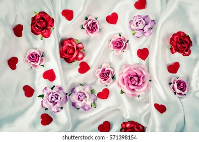 Many of roses and red heart on elegant white fabric background. Valentine concept.