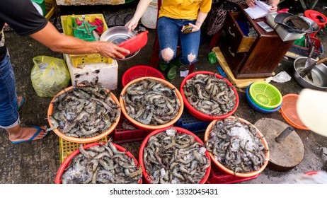 Many row,big prawns or shrimps are in the vietnamese market in the plates in the street fish market