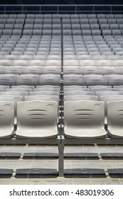 Many rows of empty plastic seats at a grandstand, viewed from the front.