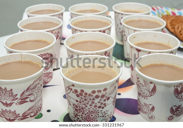 many rows of paper cups with tea milk. Indian Masala chai tea refreshing Indian blend of black tea with milk and spices. Traditional drink from China