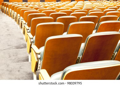 Many rows of red chairs at the empty theatre