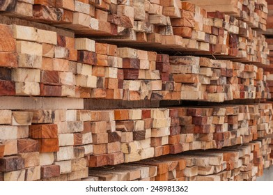 Many rows of timber are stacked high at a sawmill.