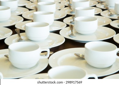 Many rows of white ceramic coffee or tea cups.
