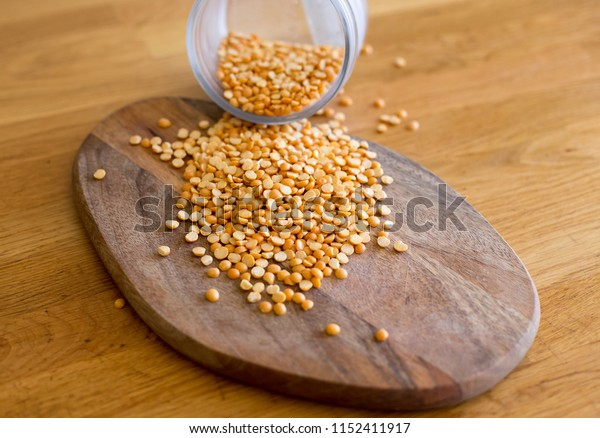 many seeds of yellow peas are scattered on a wooden board. peas poured from a round transparent glass jar without a lid