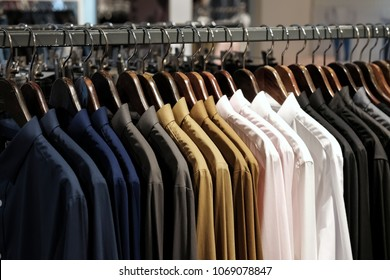 Many shirts hanging on a rack/ Row of men's suits hanging in closet. / concept of buy and sell,  business man