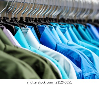 Many shirts hanging on a rack