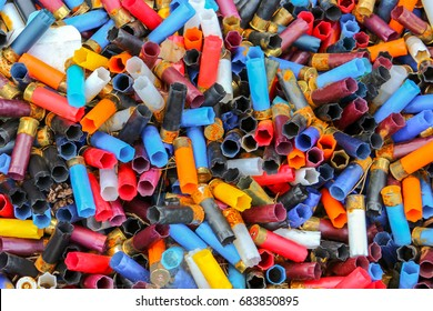 Many shotgun shells of various colors, background texture pattern with empty fired cartridges.