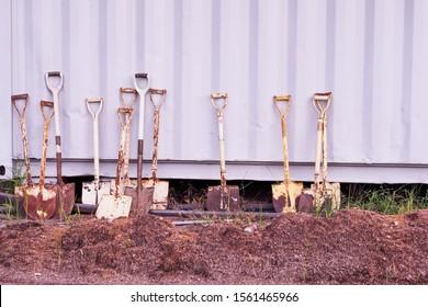 Many shovels shovel against the wall around the pile of soil.