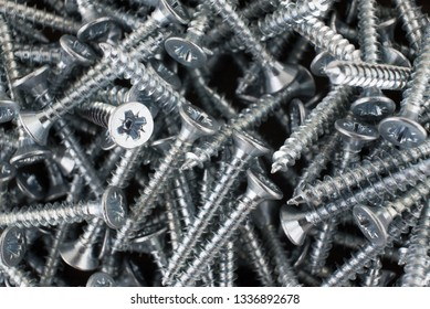 Many silver screws. Abstract background - macro photo.