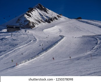 Many skiers and snowboarders descending a prepared slope from Hintertux glacier in the Austrian Alps