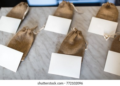 Many small brown bags of fabric and white cards.