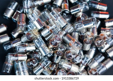 Many small incandescent bulbs lie in a heap, close-up.