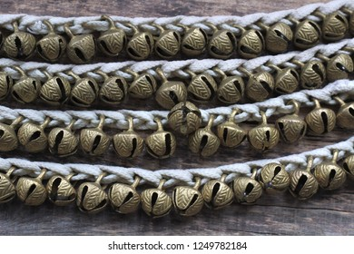 Many small Indian traditional bells for the legs strung on the lacing. Designed to reflect the rhythm in the dance. Wooden background. Top view.