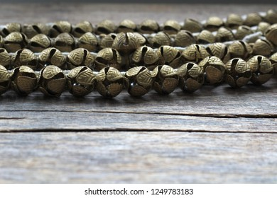 Many small Indian traditional bells for the legs strung on the lacing. Designed to reflect the rhythm in the dance. Wooden background. Place for text. Side view.