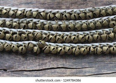 Many small Indian traditional bells for the legs strung on the lacing. Designed to reflect the rhythm in the dance. Wooden background. Top view. Place for text.