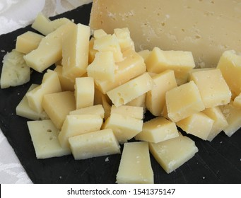 many small pieces of aged cheese and the black slate at cheese factory