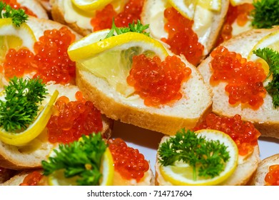 Many small sandwiches with red caviar made from white baguette and lemon with greens