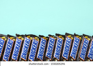 Many Snickers chocolate bars lies on pastel blue paper. Snickers bars are produced by Mars Incorporated. Snickers was created by Franklin Clarence Mars in 1930