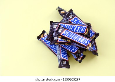 Many Snickers chocolate bars lies on pastel yellow paper. Snickers bars are produced by Mars Incorporated. Snickers was created by Franklin Clarence Mars in 1930