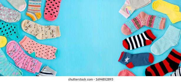 Many socks on both sides of the background. Multi-colored socks on a blue background and space for text. Clothing for autumn and winter. Socks for the cold seasons.