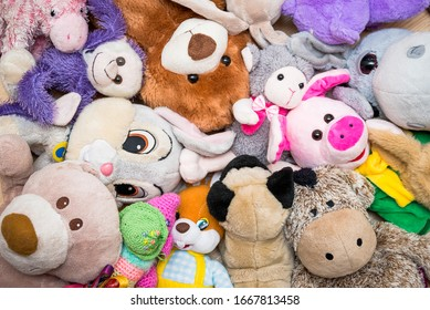 Many Soft plush fluffy toys sits on the floor in the children's room
