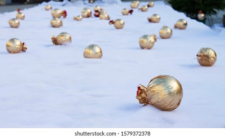 Many spherical Christmas balls wrapped in golden decoration paper on the white fabric outside in cold day|holiday