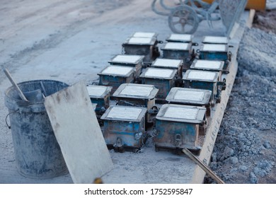 Many square cement molders to make road dividers.