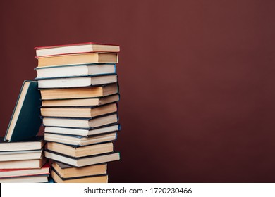 many stacks of educational books for college exams in the library on a brown background