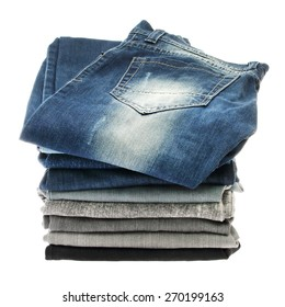 Many stacks of jeans isolated on a white background