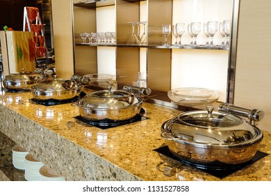 Many stainless steel cookers in the marble cupboard in the kitchen