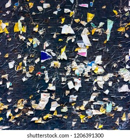 Many staples left on a black message board and torn pieces of paper