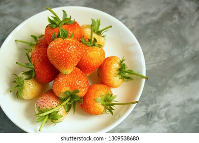 Many Strawberry in white plate on gray table. Free space for any text design.