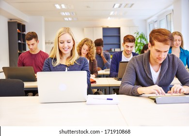 Many students in school working with computers and tablet PCs