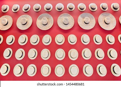 Many summer hats made of sisal ropes at red wall
