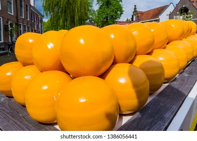 Many Super yellow Edam cheese round wheels stacked on a hand cart in Edam village in the Netherlands