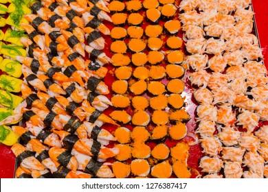 Many sushi rolls at night market street food festival of Thailand.