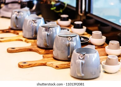 Many tea pots are assembled in a display row on wooden chopping boards in the window of a cafe