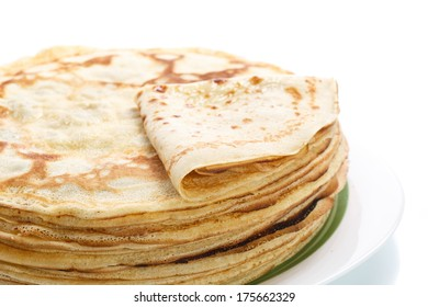 many thin pancakes on a white background