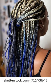 many thin plaits on the head of an African-style girl, pigtails with a kanekalon close-up on a white background, a texture of plaits