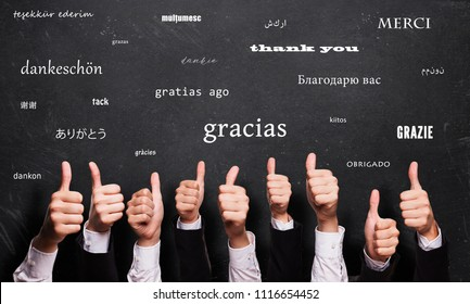 "many thumbs up in front of a blackboard with the word ""thank you"" in many languages"