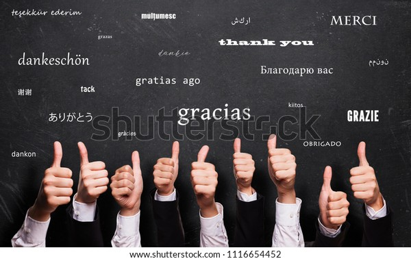 """many thumbs up in front of a blackboard with the word """"thank you"""" in many languages"""