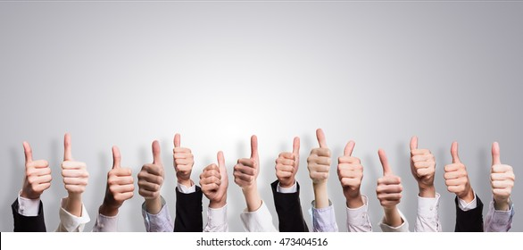 many thumbs up in front of a grey background
