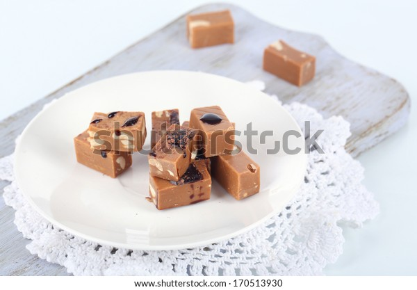Many toffee on plate on cutting board isolated on white