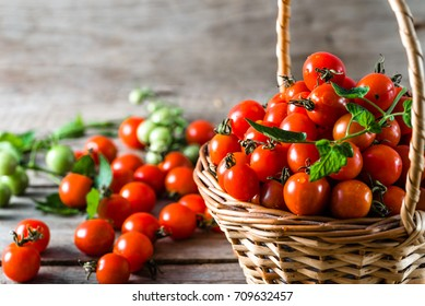 Many tomatoes called cherry tomato in the basket on wooden table, fresh organic vegetables freshly harvested from local farmers