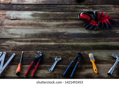 Many tools for house building and maintenance equipment with safety ear protection and handy gloves for woodworking professional on copy space, old wood background