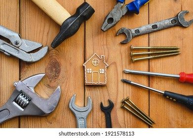 Many tools lie around a small house-shaped cookie. The concept of quality and construction or home renovation.